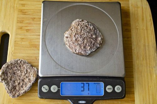 A cooked In-N-Out hamburger patty on a scale showing 37 grams weight.