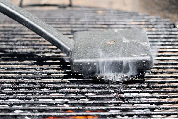 Cleaning a grill grate with a steel brush.