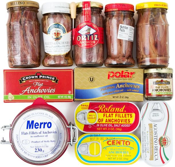 An assortment of cans and jars of anchovies.