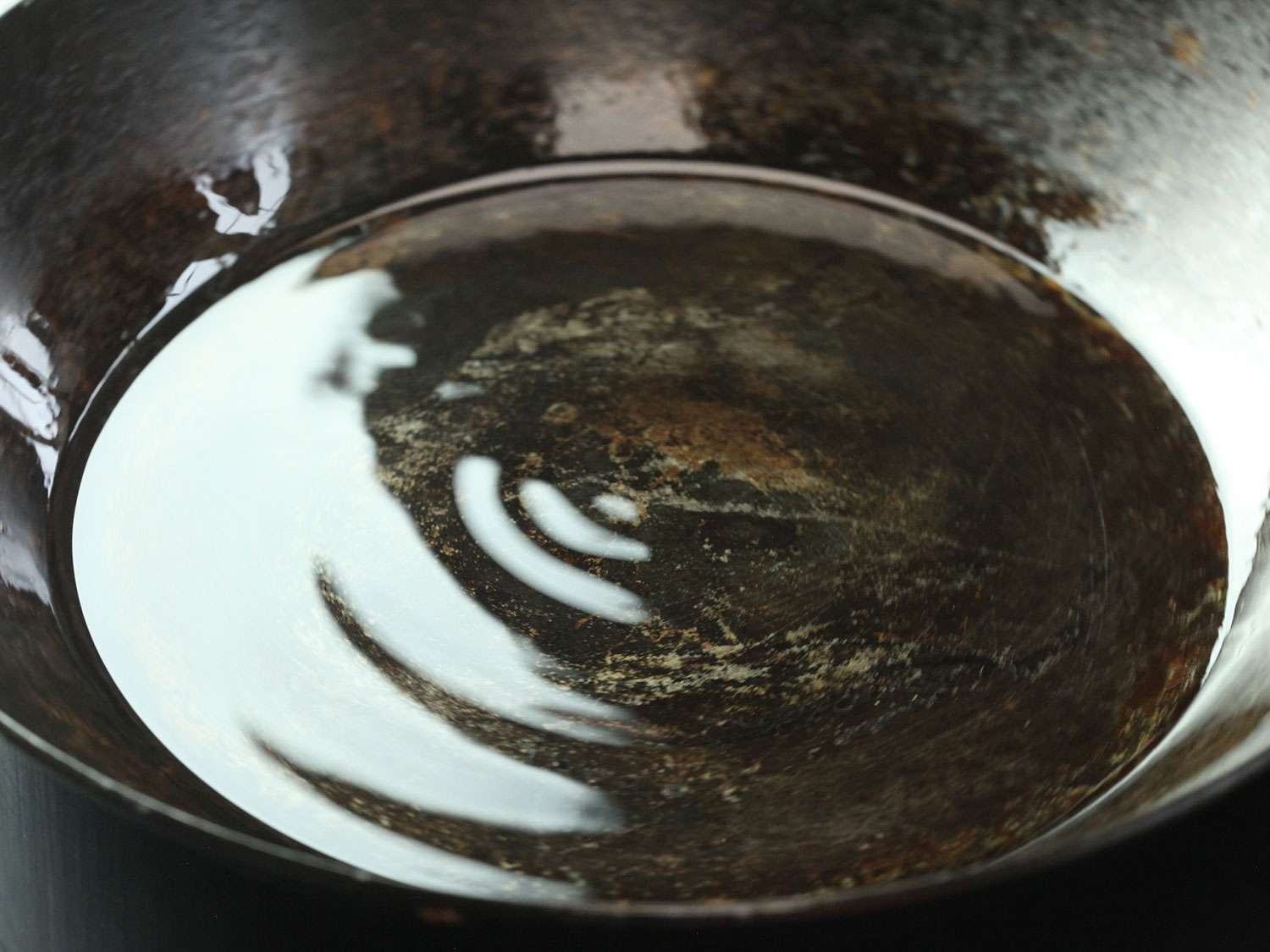 Layer of vegetable oil in a carbon steel skillet being heated until it shimmers before searing salmon.