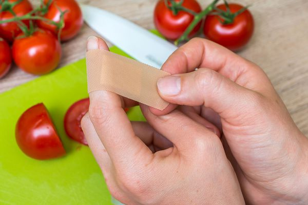 A person applying a band-aid to a finger cut on a knife while chopping tomatoes