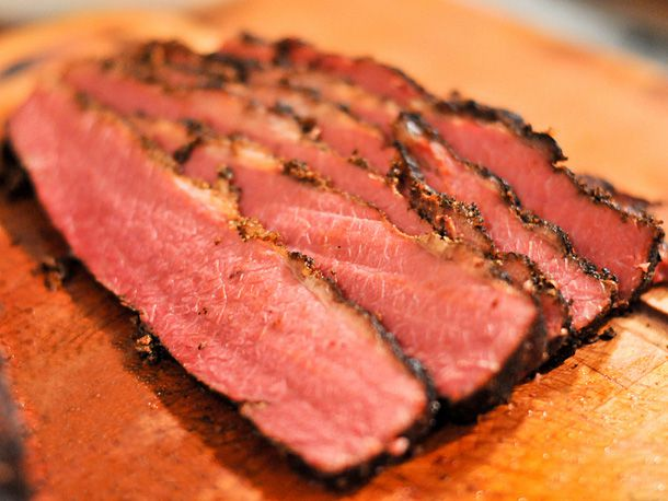 Slices of Montreal smoked meat on a cutting board.