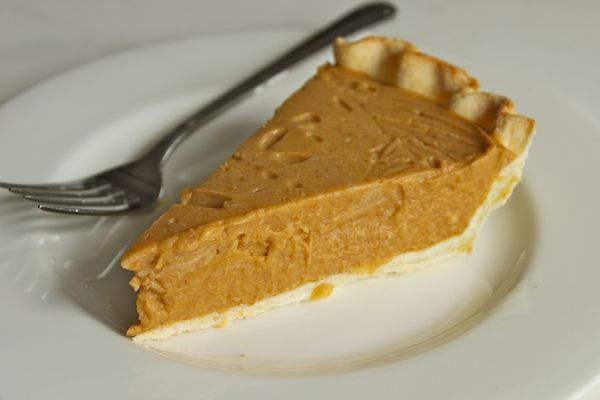A slice of dairy-free, egg-free coconut pumpkin pie on a white plate with a fork.