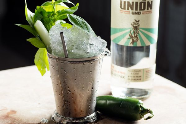 A mint julep made with basil and mezcal and garnished with basil, cucumber, and jalapeno.