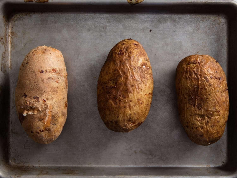 Overhead photo of baked potatoes on baking tray.