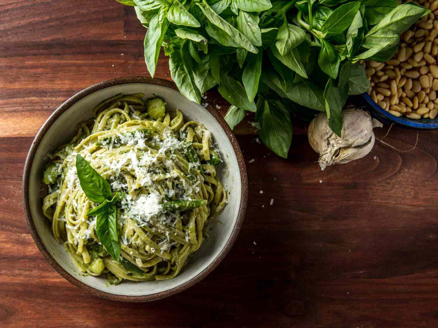 Pesto on linguine in a bowl on rustic tabletop, with fresh basil, garlic, and pine nuts on the side.