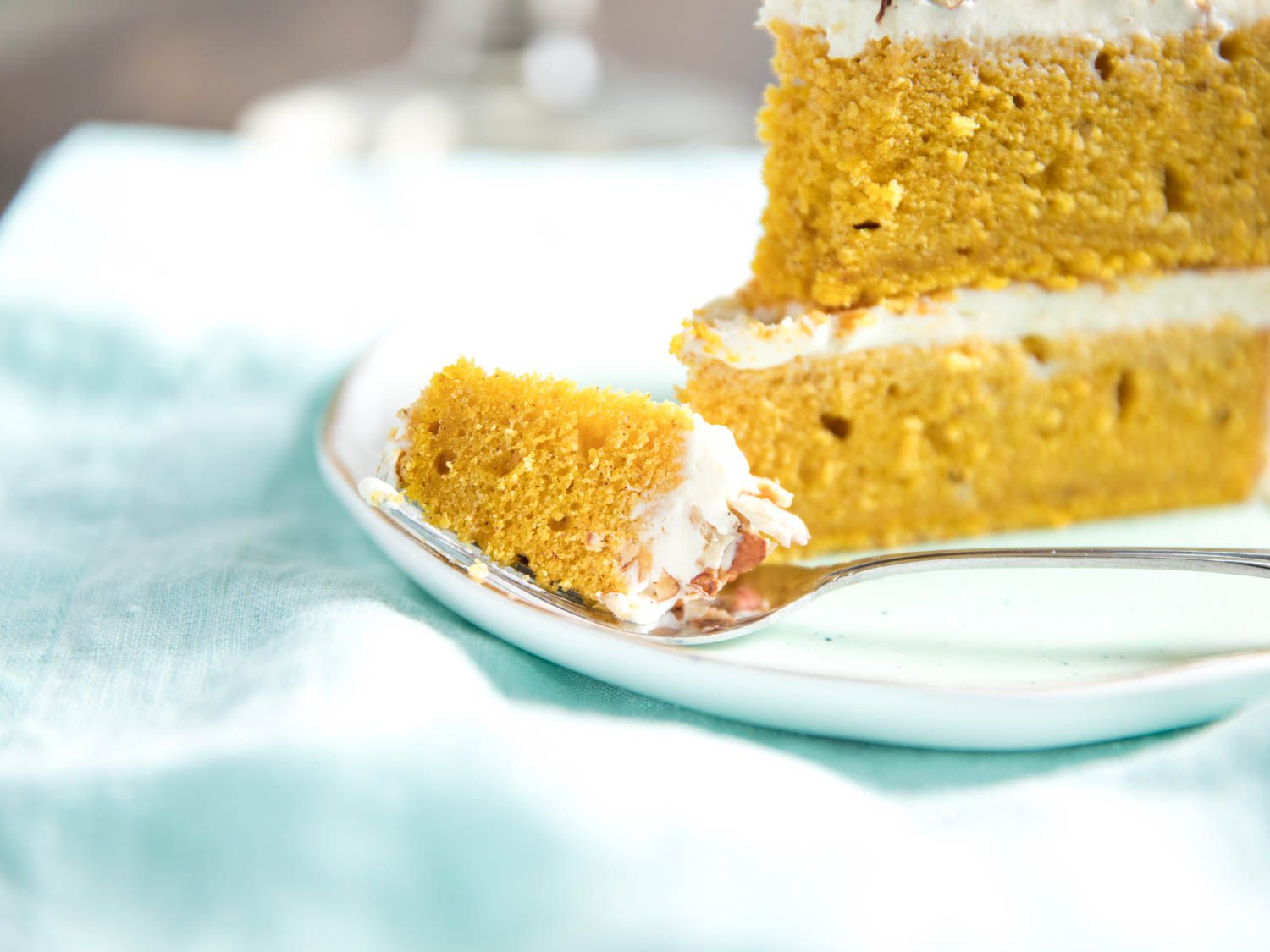 A fork spearing a bite of pumpkin layer cake, next to a wedge of cake on a plate