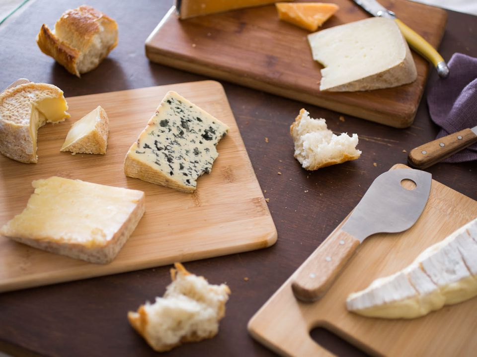 Wedges of different cheeses on cutting boards with cheese knives.
