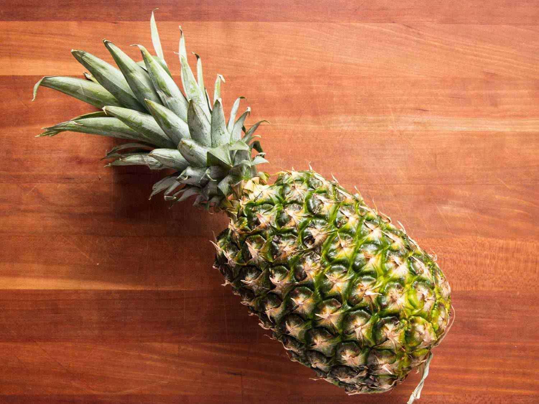 Whole pineapple on cutting board.