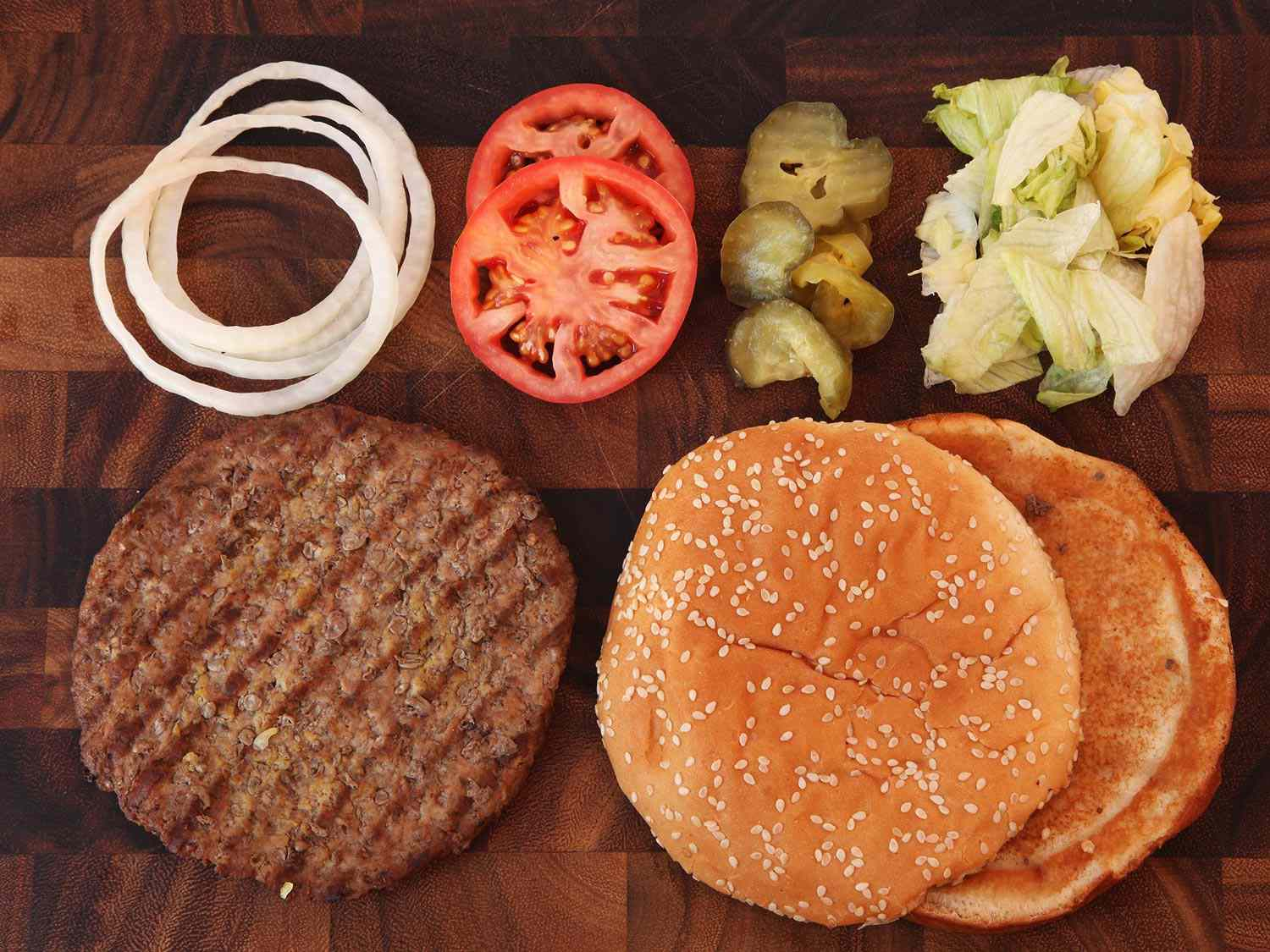 Toppings for a homemade whopper on a wood cutting board.