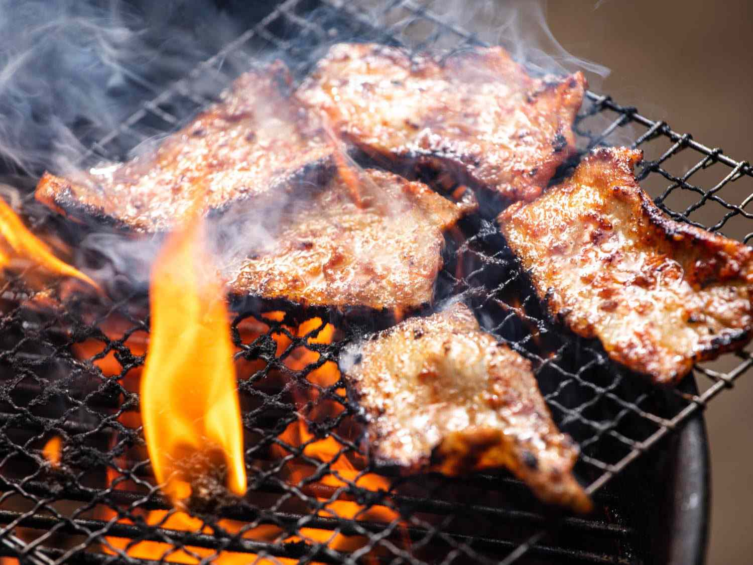 Flames licking up the sides of pieces of pork belly on the grill.