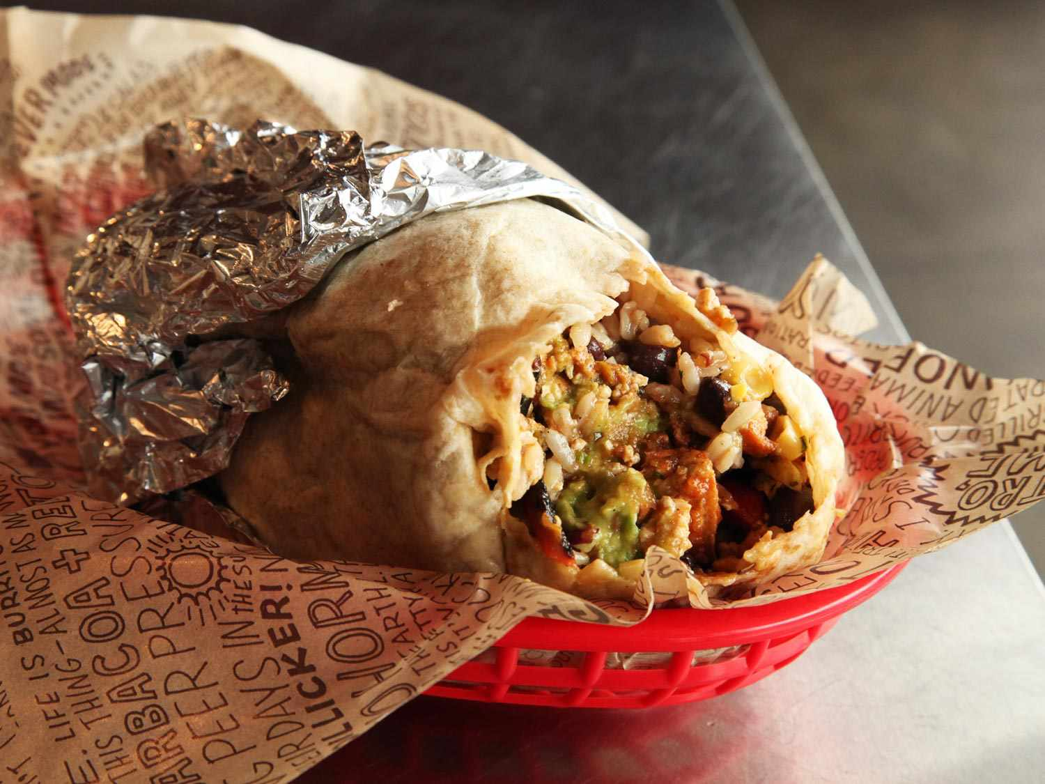 A sofritas burrito with a bite taken out of it in a red plastic tray at Chipotle