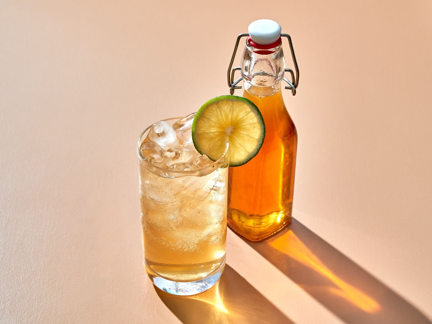 tonic syrup combined with sparkling water in a glass with ice, bottle of tonic syrup in the backround
