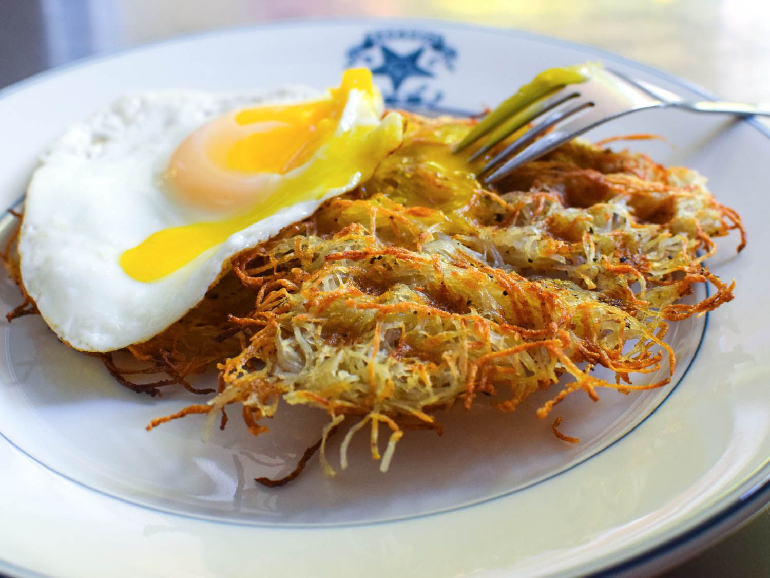 Waffle-Iron Hash Browns with a sunny side up egg on a plate.