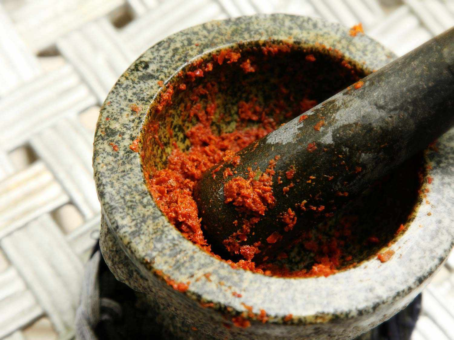 Pounding curry paste for Khao Soi Gai in a granite mortar and pestle.