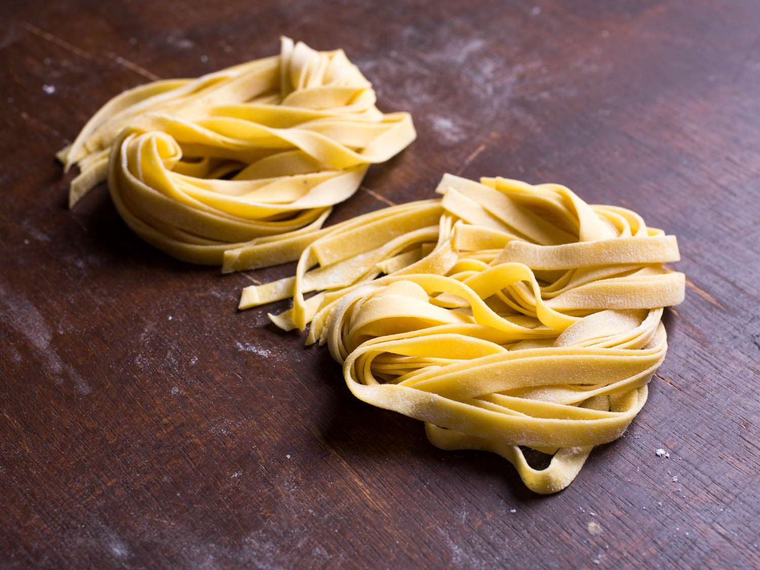 Nests of fresh pasta ribbons on a wooden surface