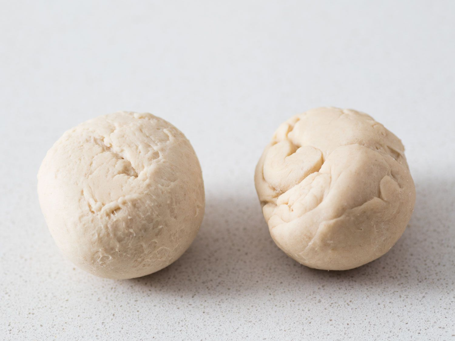 Rolled balls of bagel dough showing properly rolled ball (left) and not fully rolled ball (right).