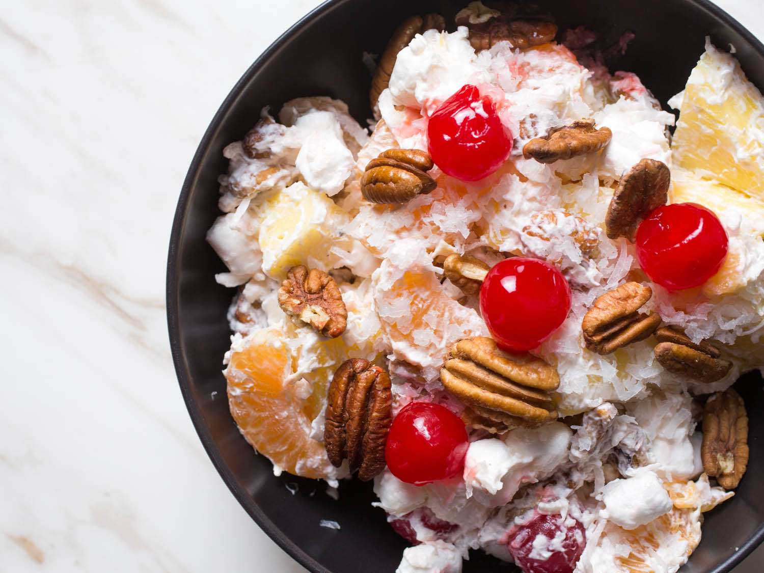 A bowl of ambrosia, a fruit salad with coconut, pineapple, pecans, orange segments, mini-marshmallows, and cherries.