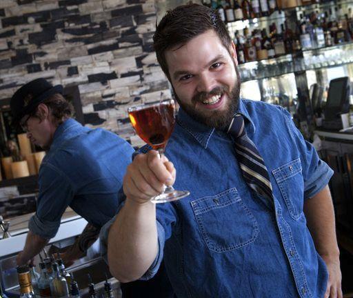 bartender holding up a drink