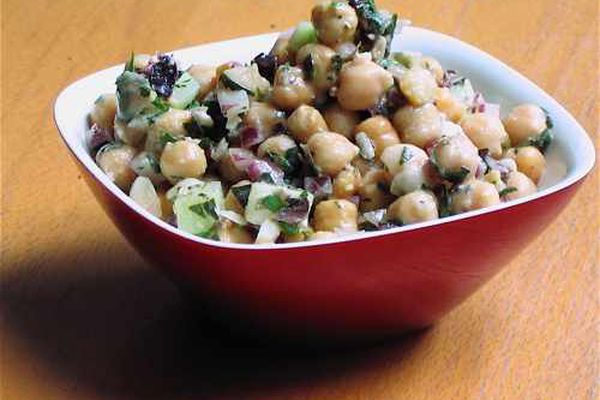 A red square bowl filled with Greek-style chickpea salad.