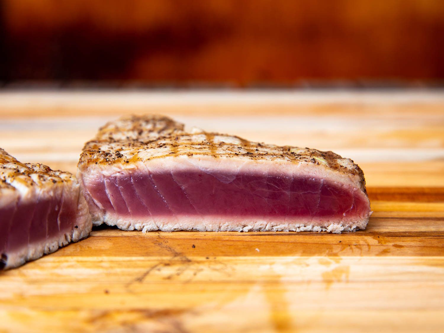 A piece of grilled tuna on the cutting board, cut in half to show the cross-section of a nicely cooked piece: seared well on the exterior, but close to raw in the middle.