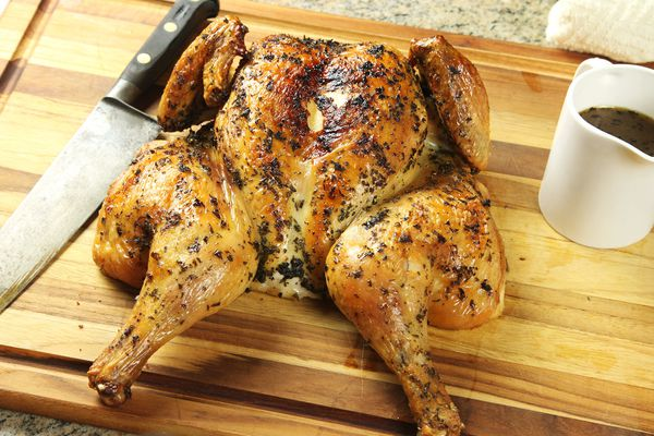 A roasted spatchcocked chicken, rubbed with herbs, on a cutting board with a knife and pot of gravy on the side.