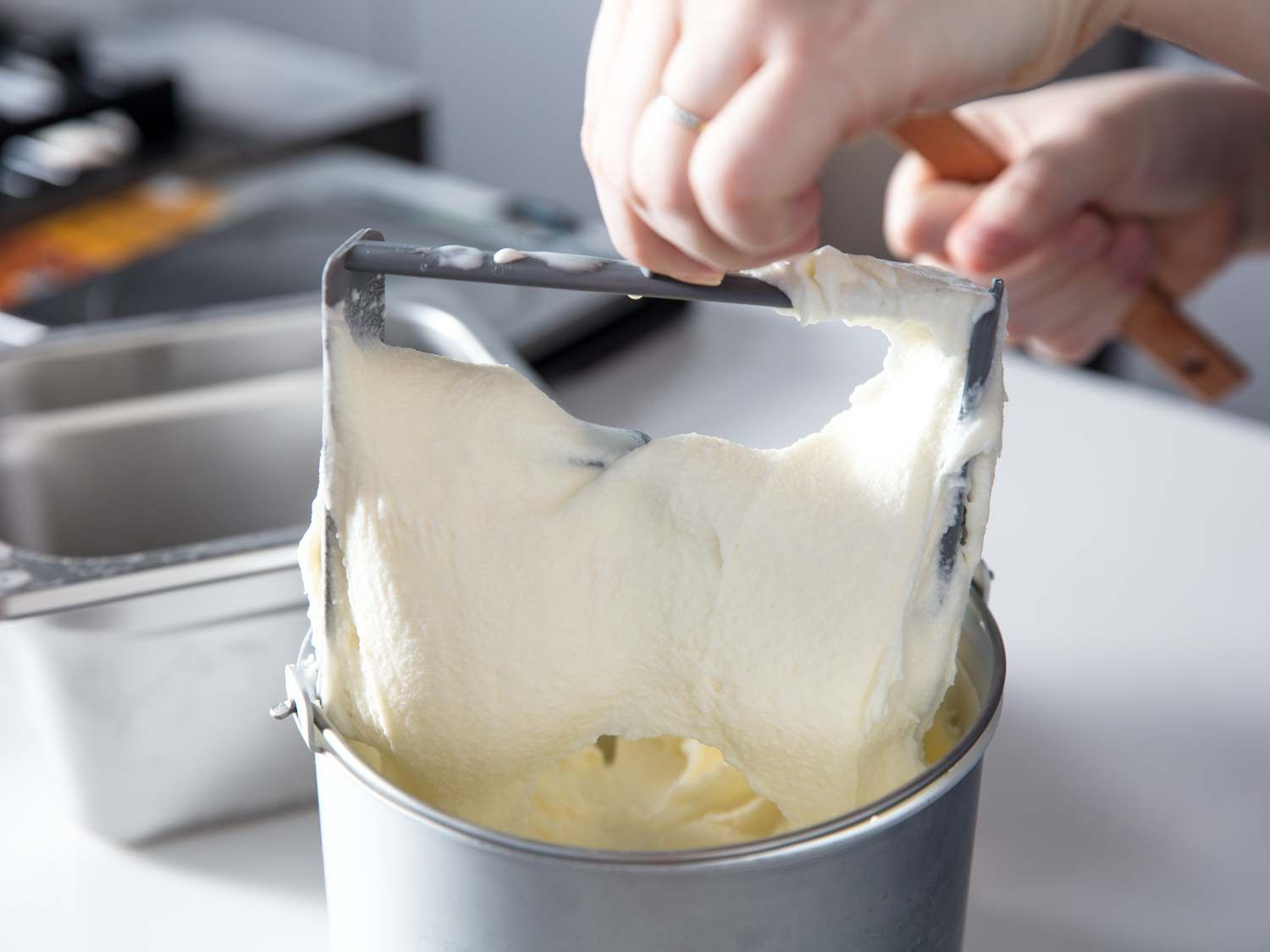 Removing the paddle from an ice cream maker full of ice cream.