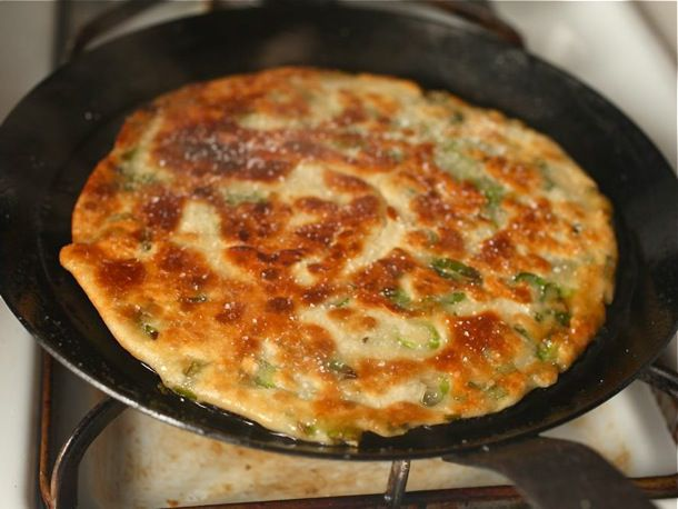 A scallion pancake cooked to an even golden-brown in a skillet.