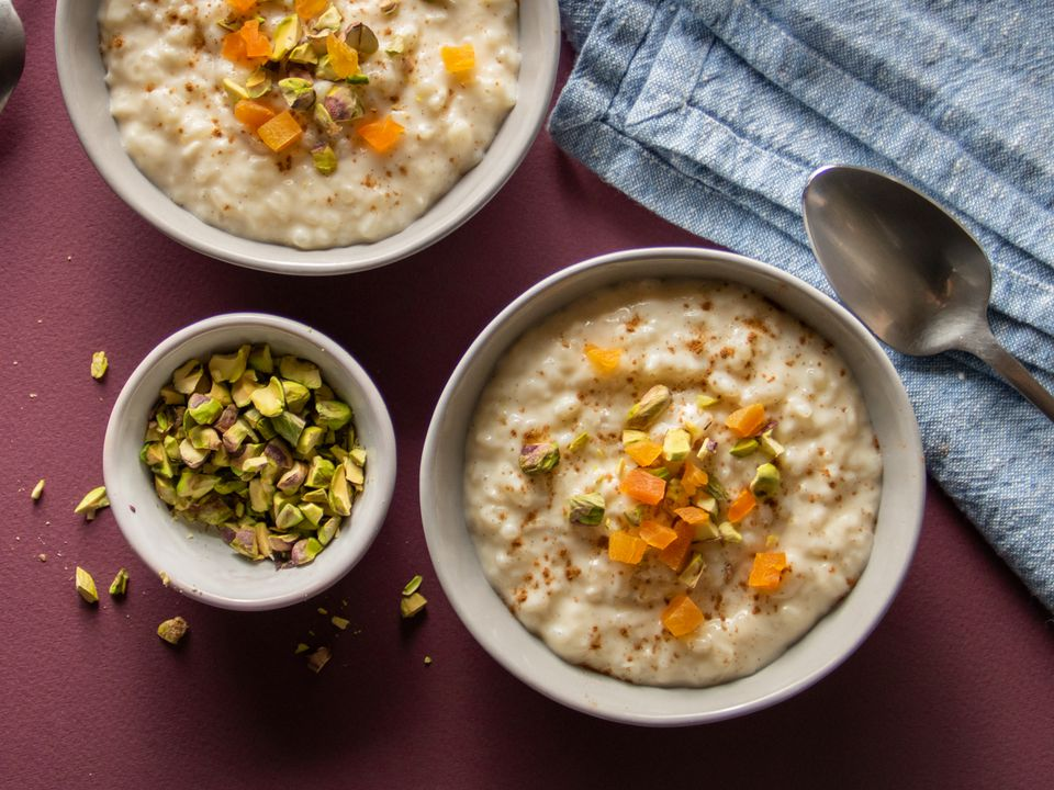 vanilla rice pudding in two bowls topped with dried apricots and pistachios