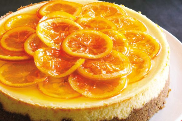 A caramelized orange cheesecake with candied orange slices on top.