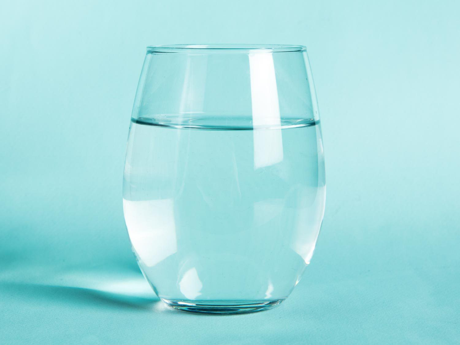 A glass of water against an aqua background