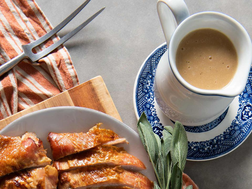 Pitcher of gravy on a blue and white plate next to a platter of roast turkey.