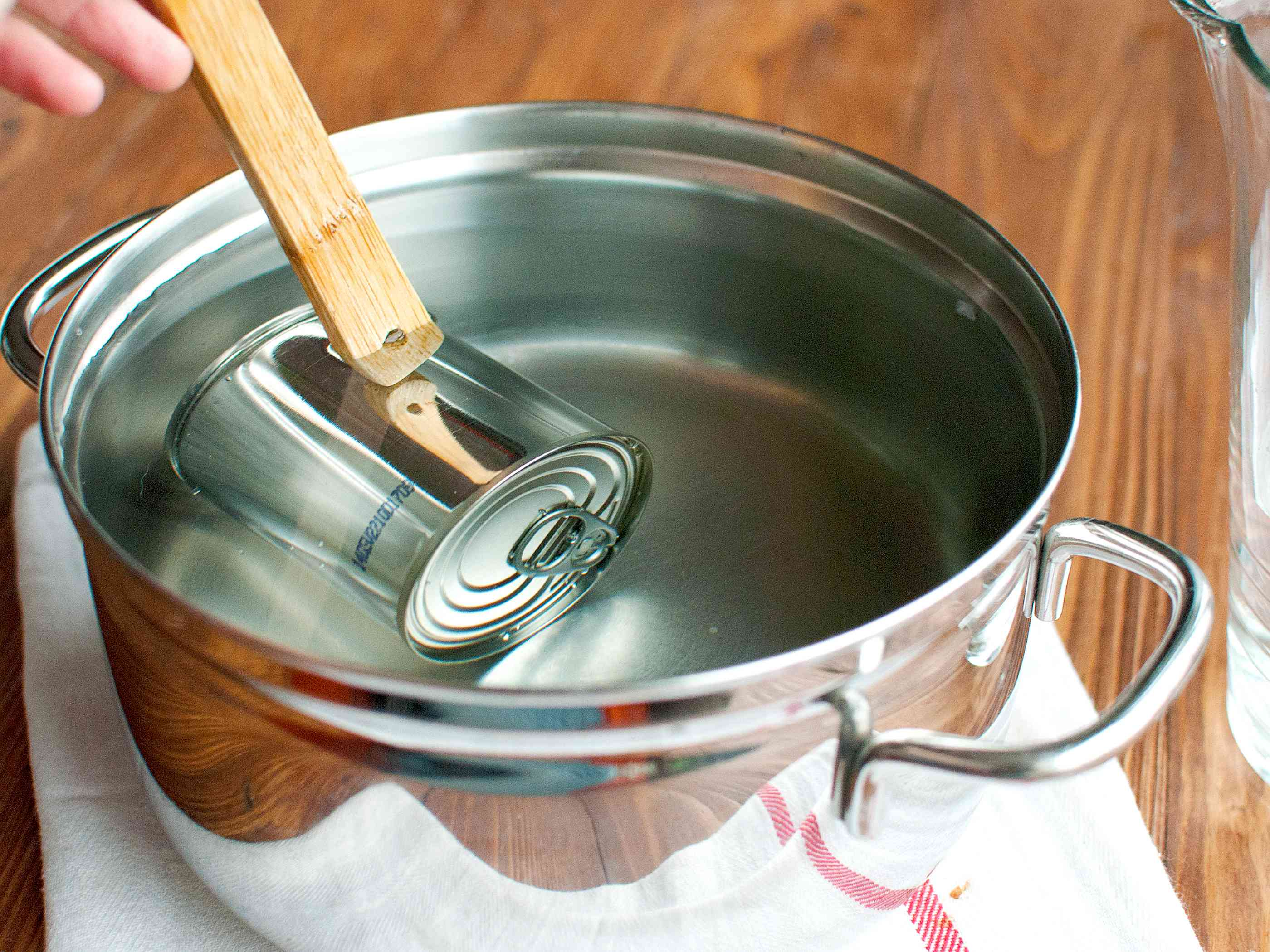 Placing a can of sweetened condensed milk in a pot of water to cook into dulce de leche
