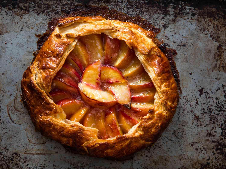 A freeform peach pie on a baking sheet