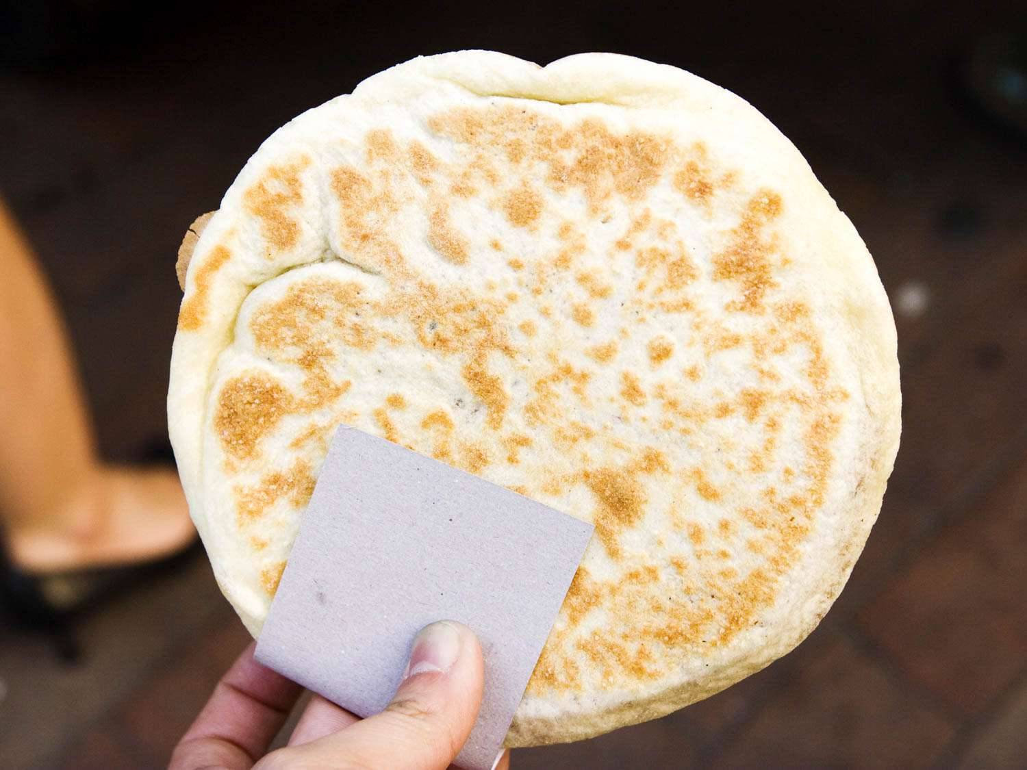 Someone holding a teok, a Korean pancake made from a sugary, yeasty wheat-based dough.