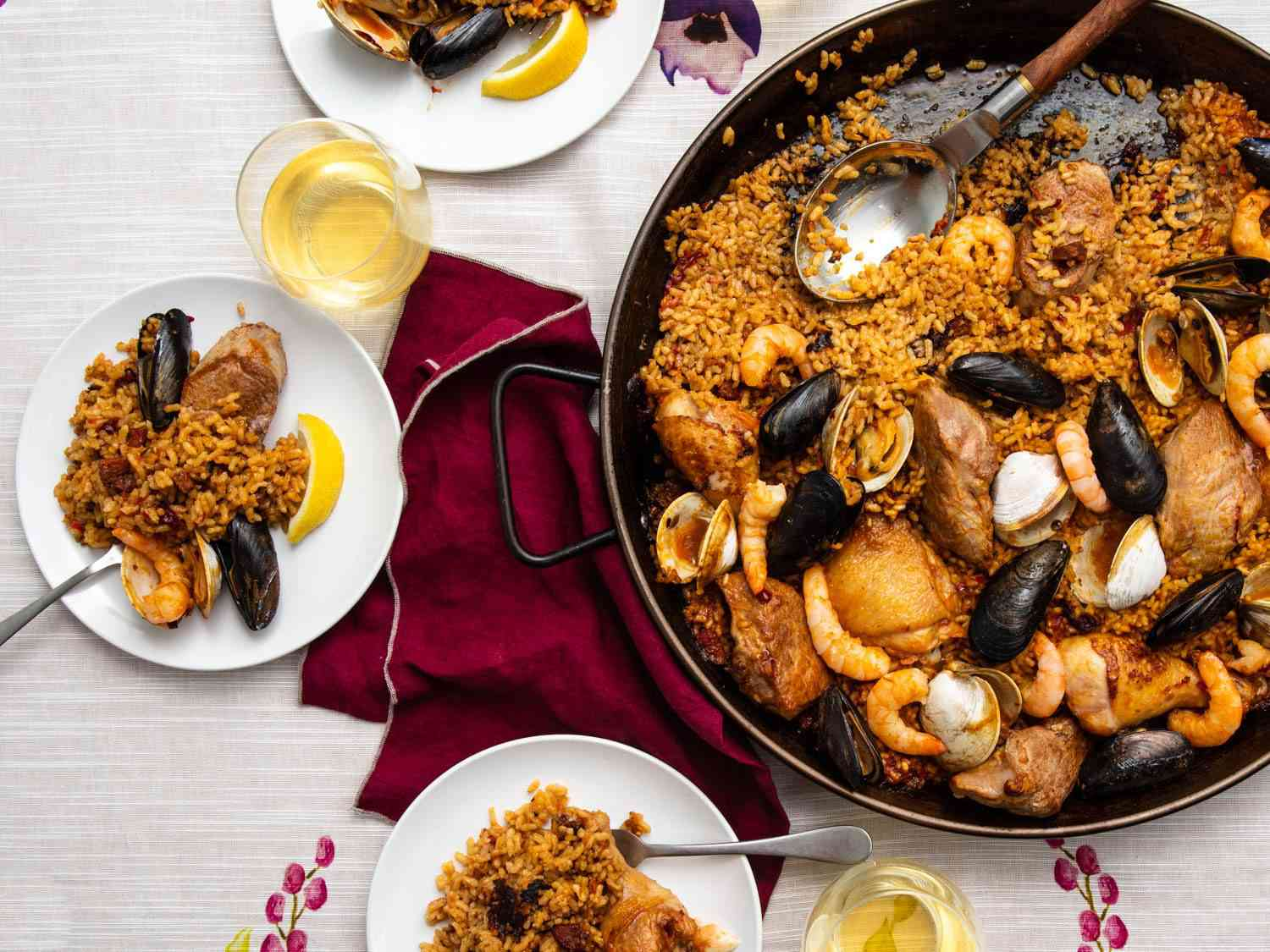 A view of a table with paella mixta served on it, showing individual plates plus the big paella pan, and wind glasses.
