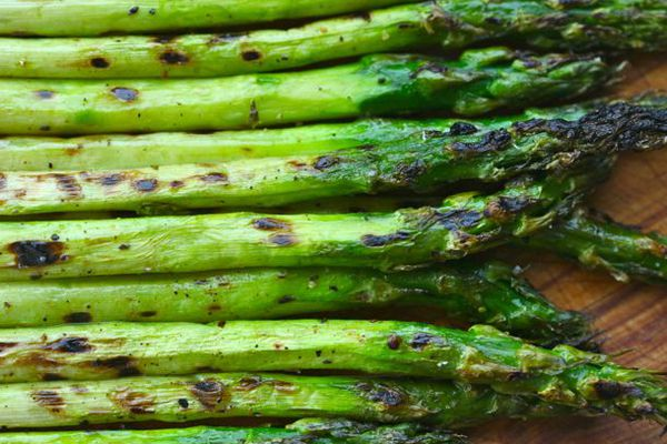 A pile of asparagus spears that have been slightly charred.