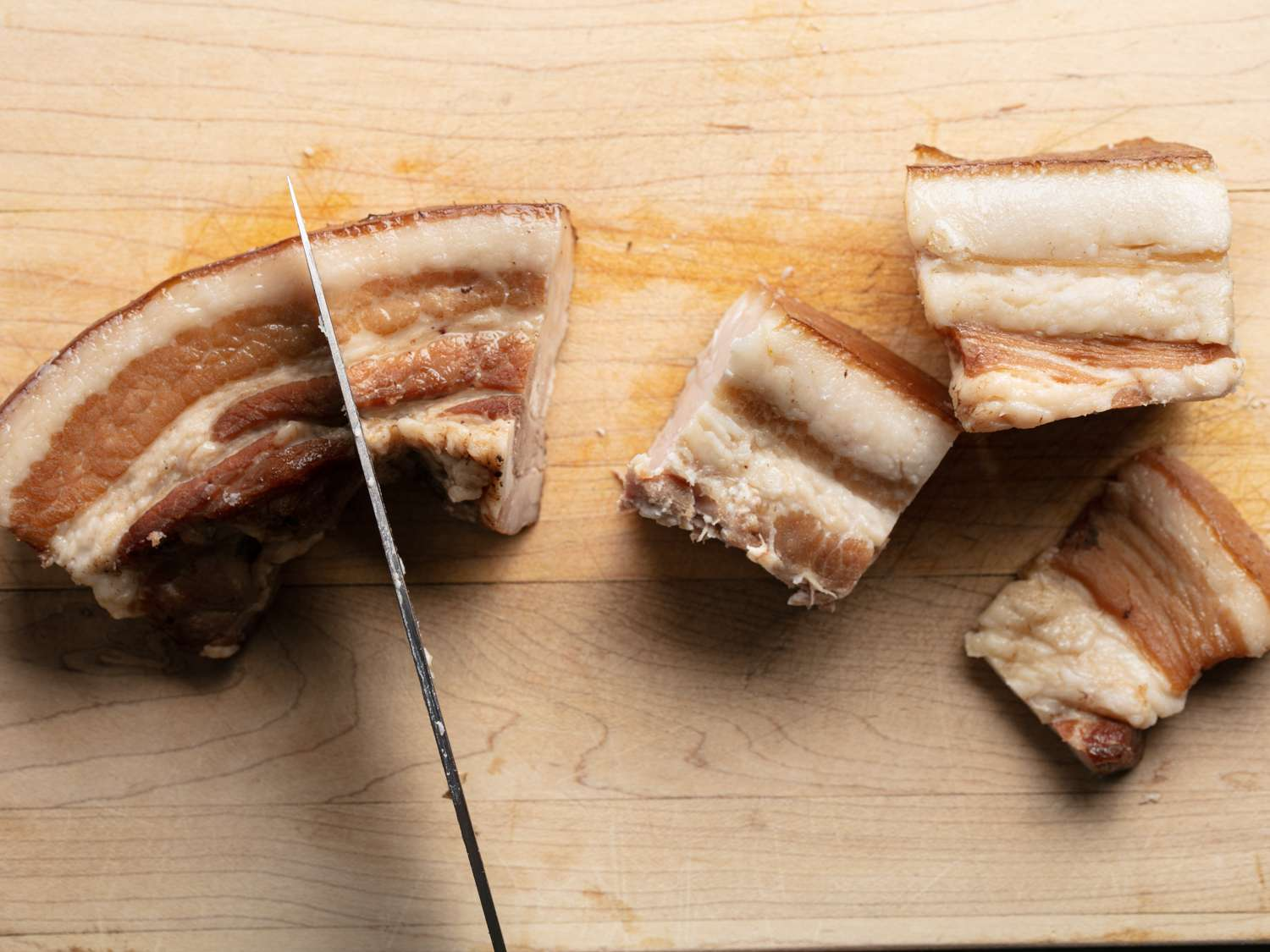 The cooked pork belly after it has been refrigerated overnight, being cut into 2 inch pieces