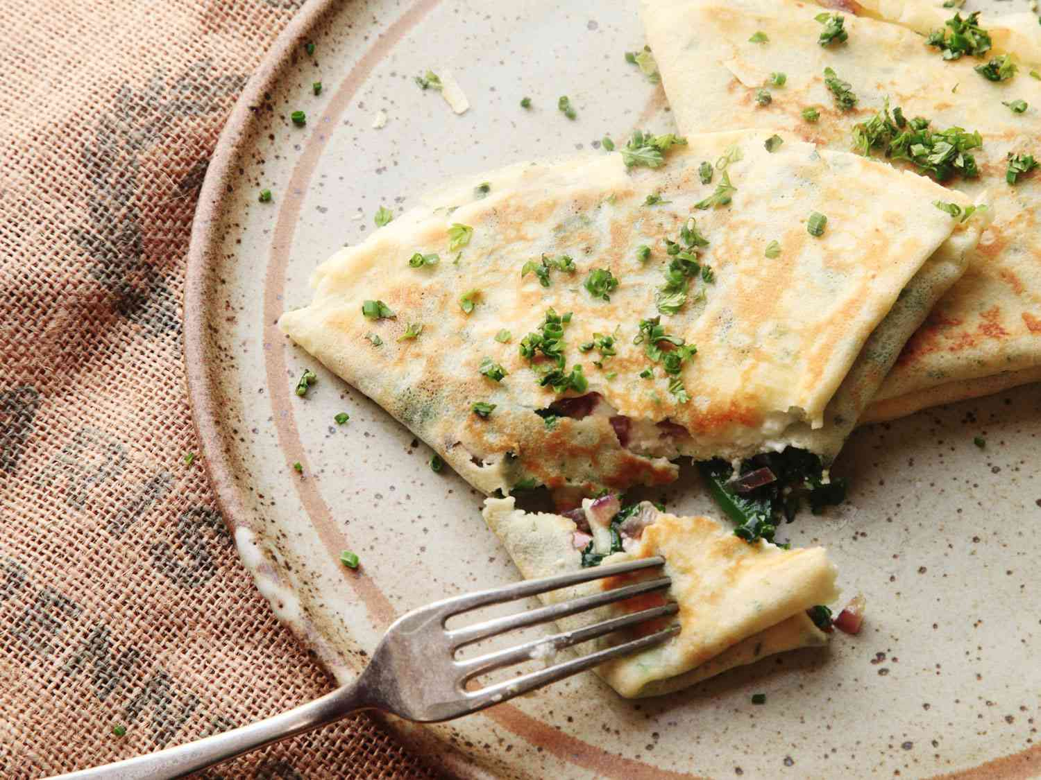 A plate of French crepes with spinach and feta, sprinkled with herbs on top.