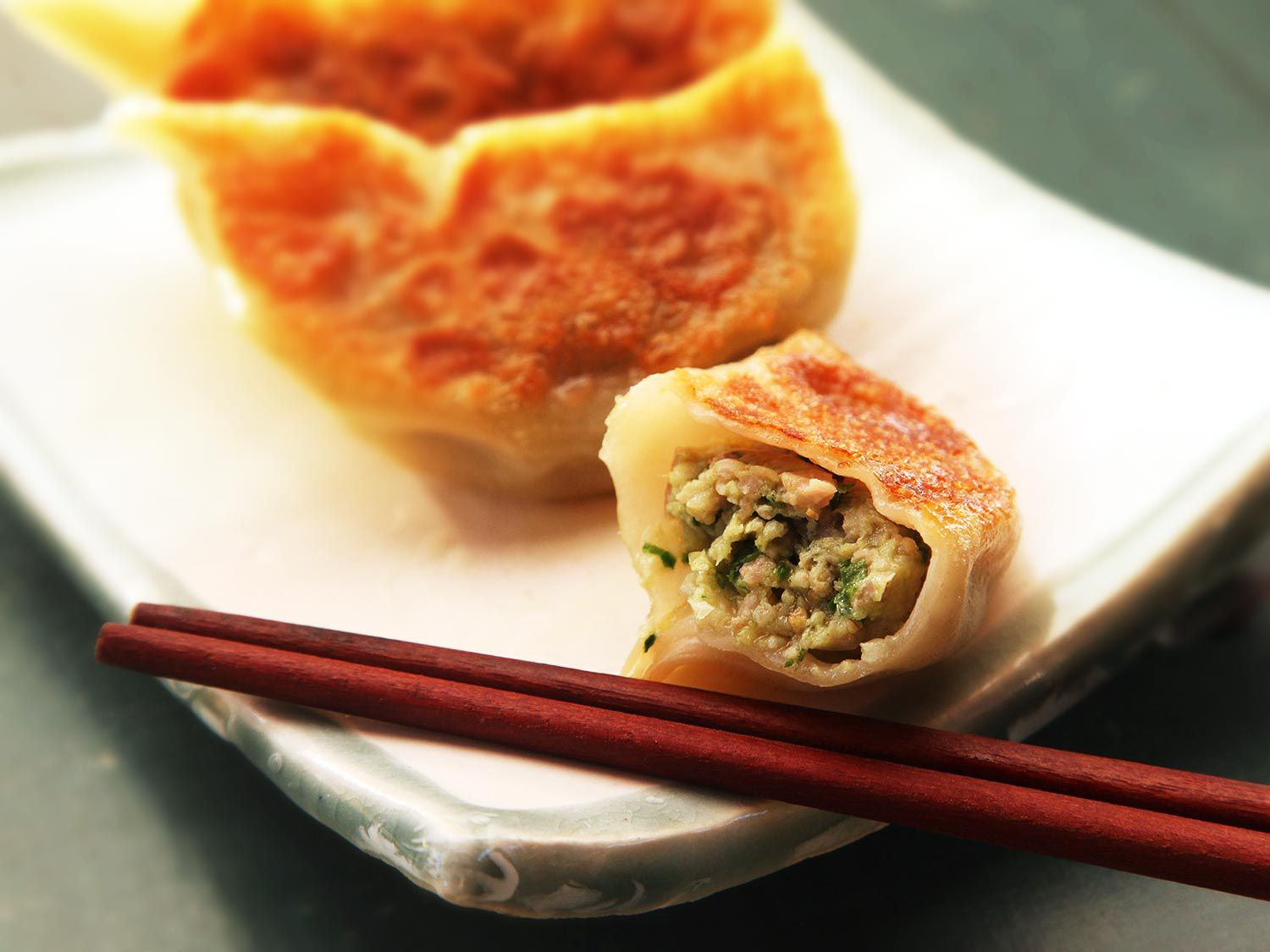 A small platter of cooked gyoza with one cut in half; the cut side is facing the camera.