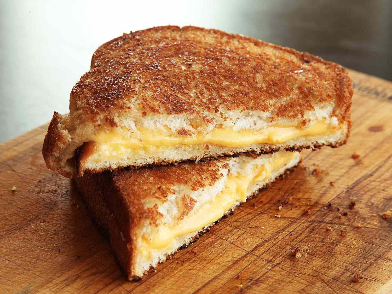 A Grilled cheese sandwich cut in half on a cutting board