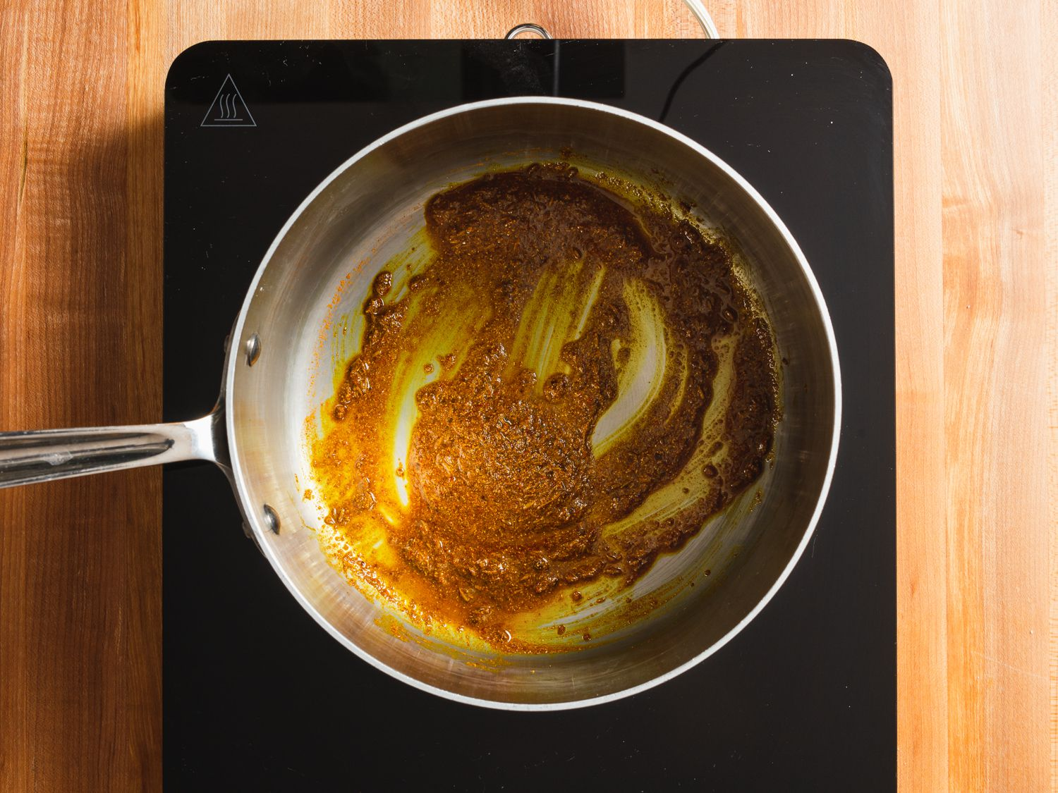 Spices for potato samosa filling being bloomed in oil in a saucepan
