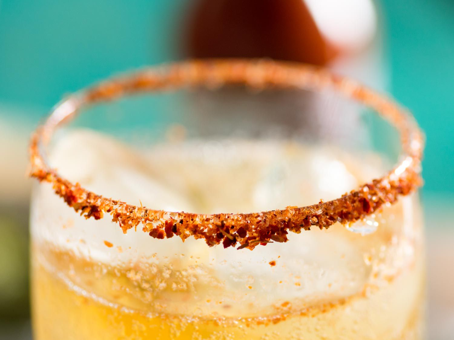 A salt- and chili-rimmed glass containing a michelada cocktail
