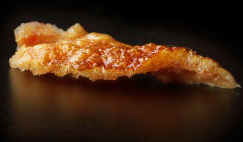 Crisp, cooked pork skin on black background.