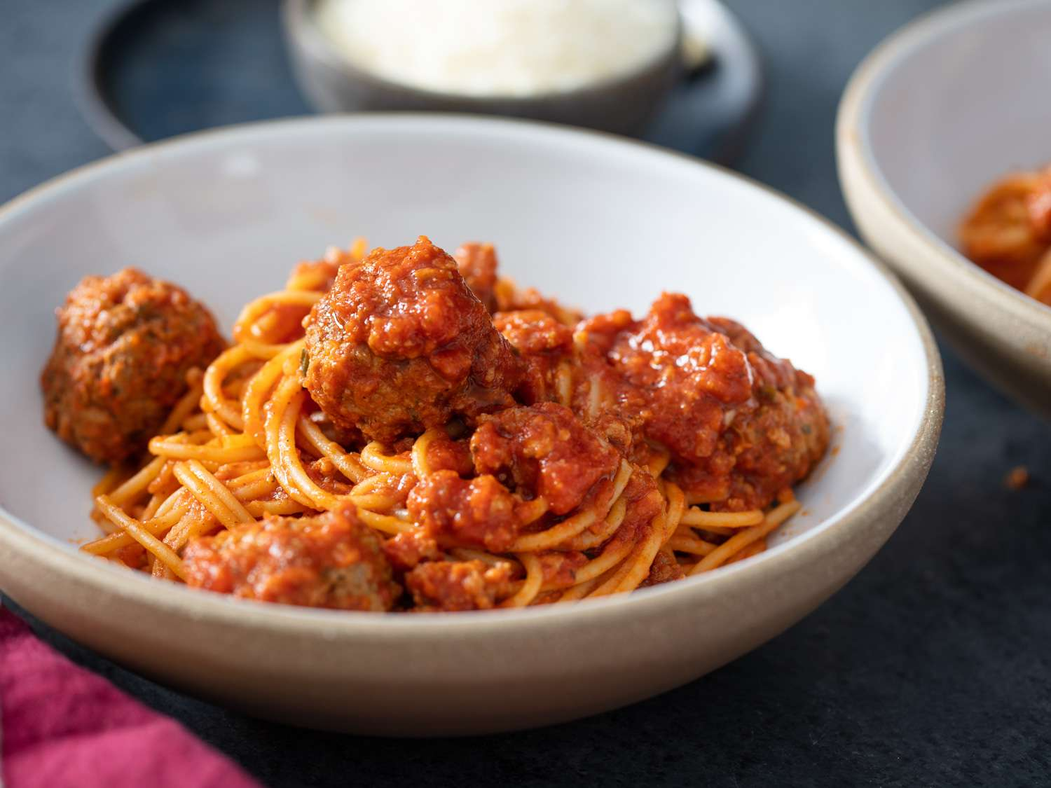 side angle of spaghetti and meatballs in a white bowl