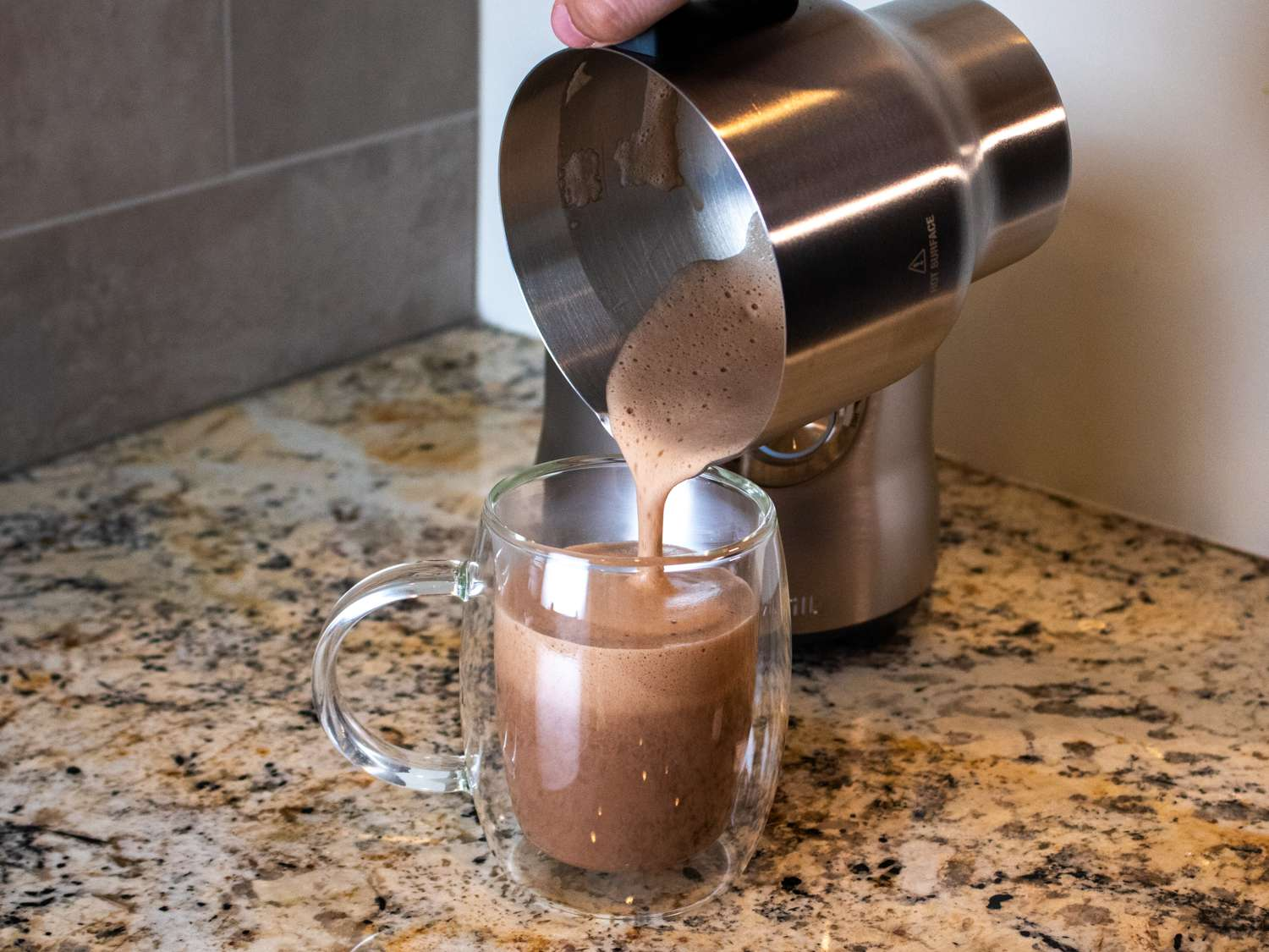 Breville pouring frothed hot chocolate into a mug