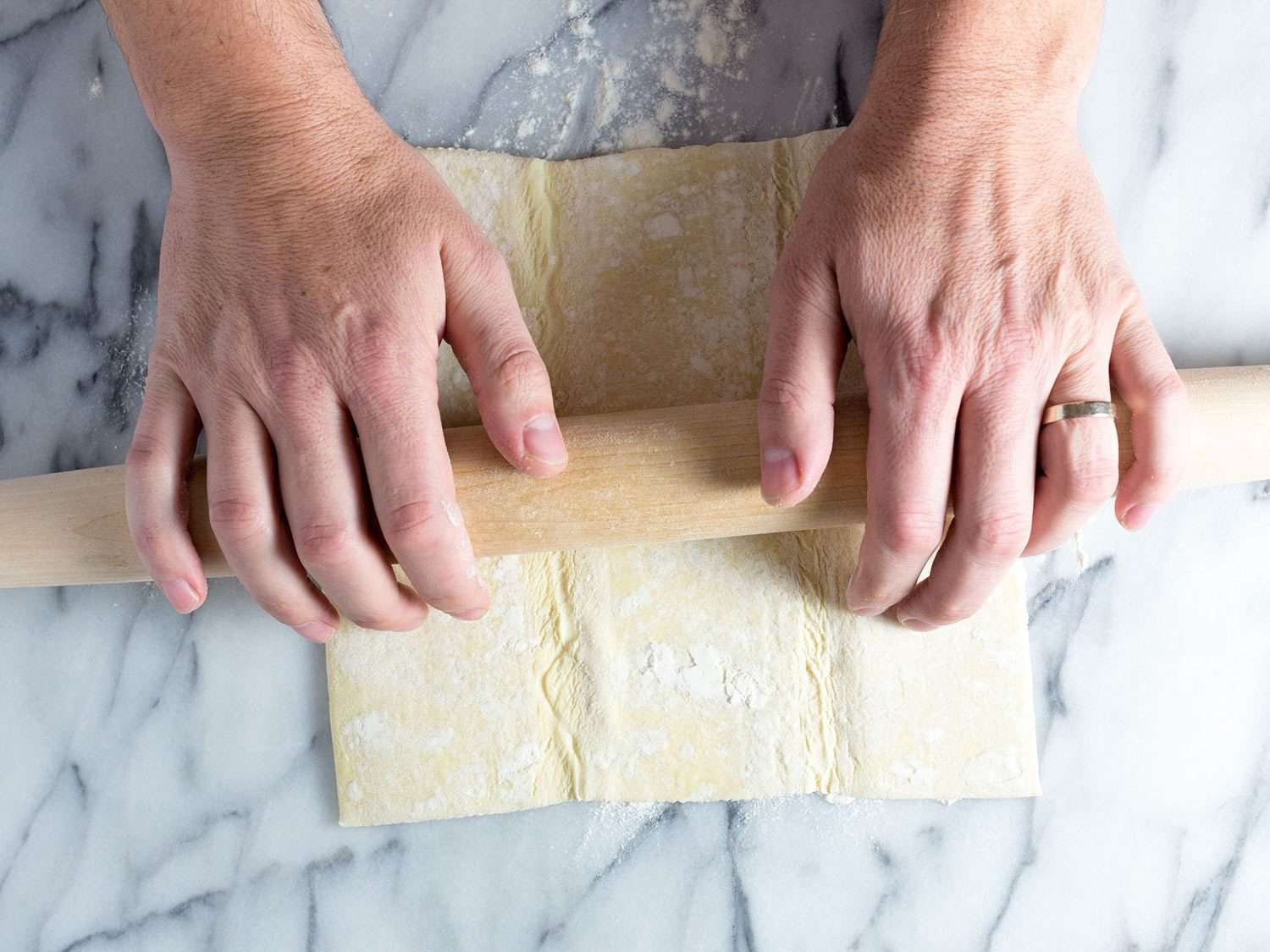 Rolling out puff pastry for baked brie.