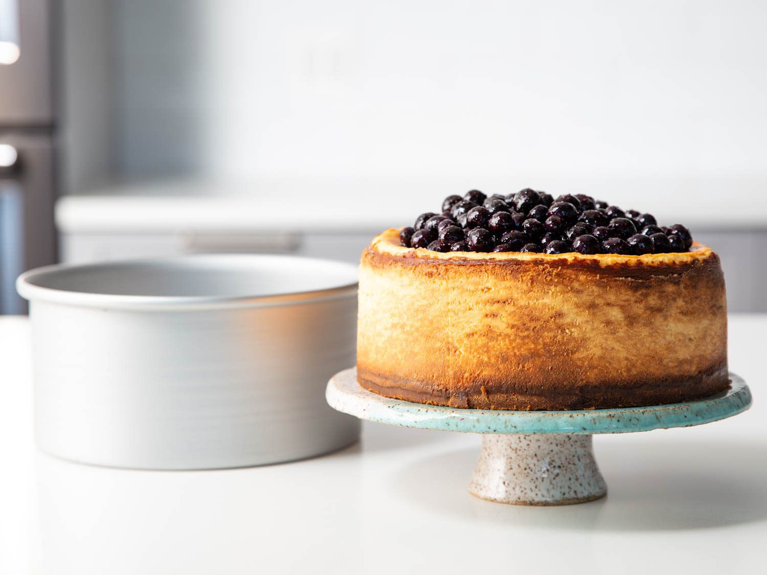 a New York style cheesecake on a pedestal, topped with blueberries