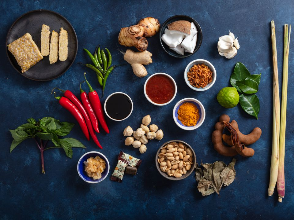 a spread of ingredients commonly used in Indonesian cooking shot from above on a dark blue background