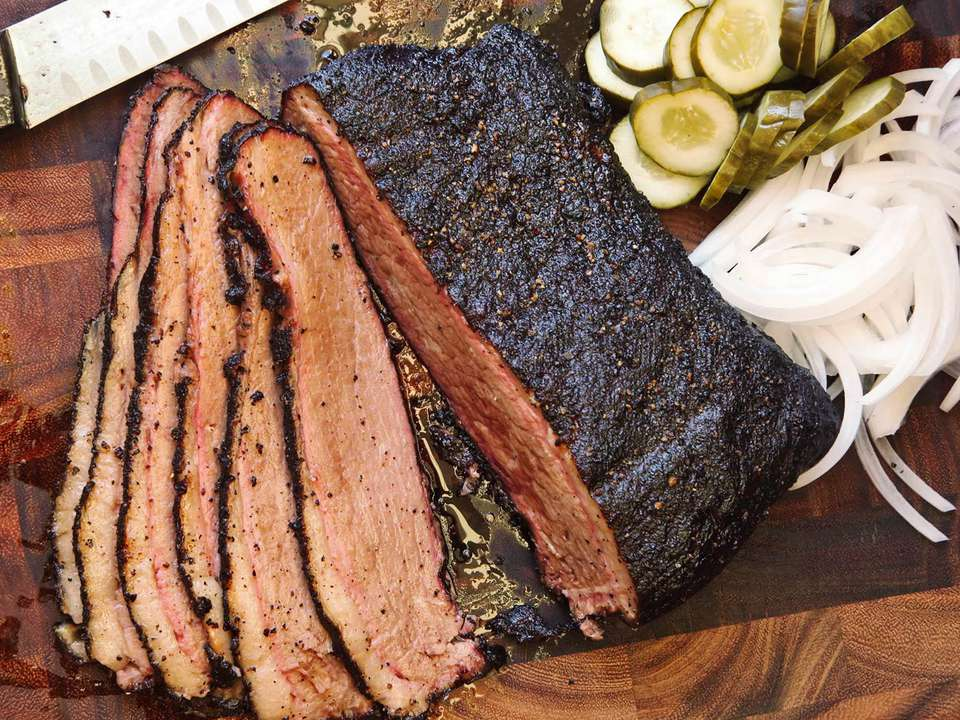Sliced smoked brisket next to sliced white onion and pickles